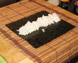 Hij weet precies hoe het moet. Legt het zeewiervel met de meest glanzende kant naar benee op de speciale Sushi-mat.