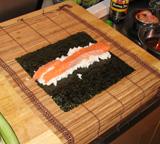 De afgekoelde Sushi-rijst erop. En daarna allerlei lekkers, zoals verse zalm.