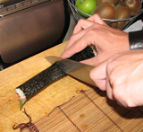 Dan snijdt ie de rol met een scherp mes in zessen